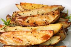 Cuñas asadas de la patata del ajo del romero Foto de archivo libre de regalías
