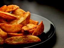 Cuñas de la patata caliente en la placa negra Fotografía de archivo
