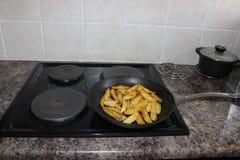 Cuñas de la patata en la estufa Foto de archivo libre de regalías