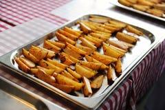Cuñas de la patata en un molde para el horno del metal Fotos de archivo libres de regalías