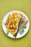 Cuñas de la patata y pescados asados de la caballa Foto de archivo