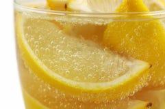 Cuñas de limón en el agua mineral de cristal Fotografía de archivo