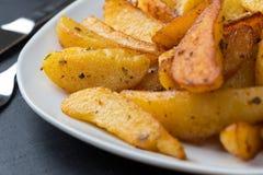 Cuñas de Potatoe en una placa Foto de archivo