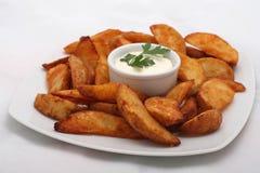 Cuñas fritas de la patata con la salsa blanca Fotos de archivo