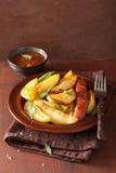Cuñas y salchicha cocidas de la patata en placa sobre la tabla rústica marrón Fotos de archivo libres de regalías