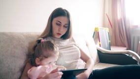 $cu: Η νέα ελκυστική μητέρα και η γλυκιά κόρη κάθονται στον καναπέ απόθεμα βίντεο