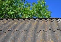 Céu azul sobre as telhas de telhado velhas do asbesto perigoso capazes de usar-se como o fundo textured Fotografia de Stock