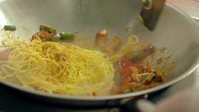 Cu, cámara lenta: el cocinero prepara las pastas en sartén, en aceite, con las verduras frescas almacen de metraje de vídeo