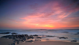 Céu carmesim sobre a praia rochosa Fotos de Stock Royalty Free