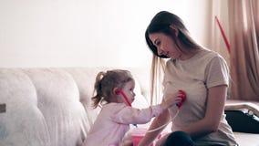 Cu: De jonge aantrekkelijke moeder en de zoete dochter spelen de rol van arts en patiënt stock video