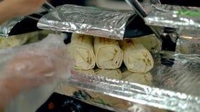 CU: El cocinero calienta el shawarma cocinado en la parrilla almacen de metraje de vídeo