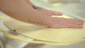 CU: Hanen rullar ut pizzadegen med hans händer stock video