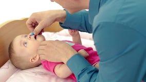 CU : Jeunes jeux de père avec peu de fille douce, qui se trouve sur la table de couche-culotte Il s'égoutte doucement la médecine banque de vidéos