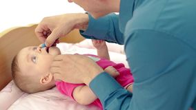 Cu: Jonge vaderspelen met weinig zoete dochter, die op luierlijst ligt Hij druipt zacht geneeskunde in haar neus stock footage