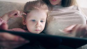 $cu, 4k: Η νέα ελκυστική μητέρα και η γλυκιά κόρη κάθονται στον καναπέ και διδάσκουν χρησιμοποιώντας έναν υπολογιστή ταμπλετών φιλμ μικρού μήκους
