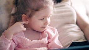 CU 4k: Den unga attraktiva modern och den söta dottern sitter på soffan och utbildar genom att använda en minnestavladator arkivfilmer