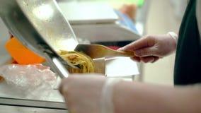CU: Koch verschiebt die Nudeln mit Gemüse in das Paket stock video footage