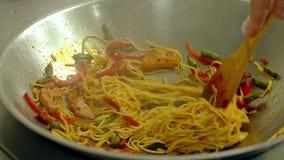 Cu, langzame motie: de kok bereidt noedelsdeegwaren in een pan, in olie, met verse groenten voor stock video