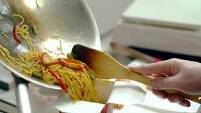 CU : Le cuisinier décale les nouilles avec des légumes dans l'emballage, pour davantage de livraison banque de vidéos