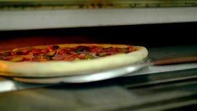 CU : Le cuisinier met la pizza dans le four pour faire et ferme la porte banque de vidéos
