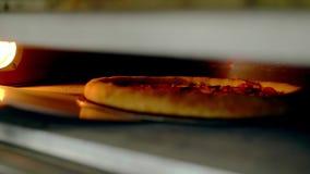 CU : Le cuisinier ouvre le four, qui fait la pizza cuire au four, et le tourne clips vidéos