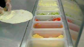 CU : Le cuisinier prépare le shawarma, ou le wok, met des légumes sur un gâteau plat avec la mayonnaise banque de vidéos