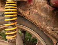 CU of muddy weathered grungy rear wheel and yellow spring-type shock absorber of light motorcycle in Asia Stock Photography
