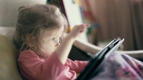 Cu: portret van mooi meisje, kind dat op bank onder deken ligt en op tabletcomputer speelt stock video