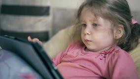 Cu: portret van mooi meisje, kind dat op de bank onder deken ligt en op een tabletcomputer speelt stock videobeelden