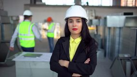 Female engineer standing and male engineer using digital tablet in background. Portrait of female engineer. airduct of
