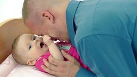 CU: Unga faderlekar med den lilla söta dottern, som ligger på en ändrande tabell Han kysser henne, dem skrattar arkivfilmer