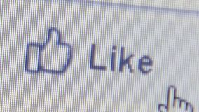 CU user moving hand icon cursor to click on a Facebook `Like` icon. Macro level extreme close up of user moving hand icon cursor to click on a Facebook `Like` stock video