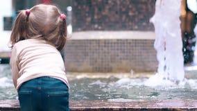 CU, vue arrière, mouvement lent : Peu fille douce jouant avec de l'eau près de la fontaine Les pulvérisateurs arrosent avec une m banque de vidéos