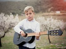 Cuacasian pojke med gitarren i parkera utomhus arkivbild