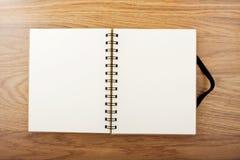 Cuaderno abierto con la banda elástica negra una tabla Imagen de archivo
