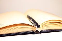 Cuaderno abierto con la pluma negra Fotos de archivo libres de regalías