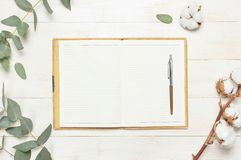 Cuaderno abierto con las páginas en blanco, la pluma, la ramita del eucalipto y las flores del algodón en la endecha plana de mad imagenes de archivo
