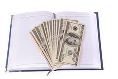Cuaderno abierto con los billetes de banco de los dólares Imagen de archivo