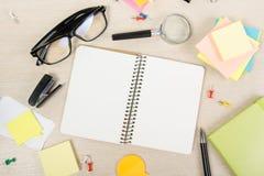 Cuaderno abierto del espacio en blanco blanco Escritorio de la tabla de la oficina con el sistema de fuentes coloridas, taza, plu Imagen de archivo libre de regalías
