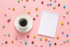 Cuaderno abierto del espacio en blanco con una taza de café y de caramelo colorido en p Fotos de archivo