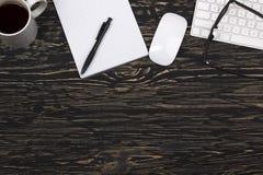 Cuaderno abierto, vidrios, taza, teclado de ordenador moderno y ratón blanco Fotografía de archivo libre de regalías