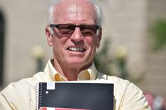 Cuaderno adulto sonriente de Wearing Sunglasses With del profesor de sexo masculino foto de archivo libre de regalías