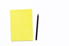 Cuaderno amarillo y lápiz negro en un fondo blanco Concepto mínimo del negocio para la oficina Fotografía de archivo