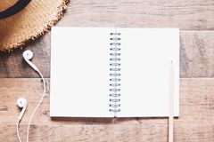 Cuaderno, auriculares y sombrero en blanco en la tabla de madera, planeamiento del viaje, forma de vida Imagen de archivo libre de regalías