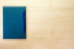 Cuaderno azul y pluma azul en el escritorio Imagen de archivo libre de regalías