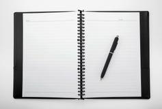 Cuaderno blanco en blanco con una pluma imagen de archivo libre de regalías