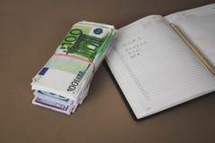 cuaderno blanco en el fondo de cientos cierres del efectivo del euro para arriba fotos de archivo libres de regalías