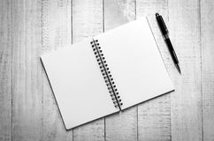 Cuaderno blanco y negro del espacio en blanco de la visión superior y pluma negra Imágenes de archivo libres de regalías
