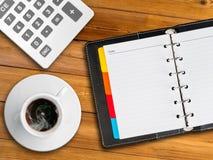 Cuaderno blanco y taza blanca de café caliente Foto de archivo