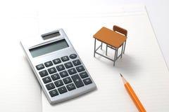 Cuaderno, calculadora, lápiz y escritorio miniatura Foto de archivo